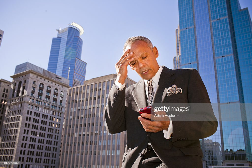 A middle aged businessman using a cell phone. : Stock Photo