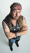 middle aged caucasian adult male with an earring and  long hair and a tatoo on both arms wears an american flag headband and a leather vest with motorcycle symbols as he folds his arms and looks up at the camera with an impudent expression