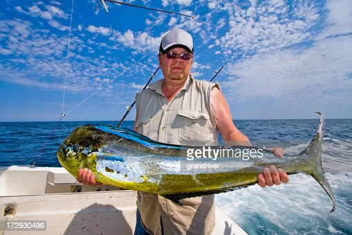 Middle aged caucasian fisherman with mahimahi dorado or for Florida fishing license for seniors