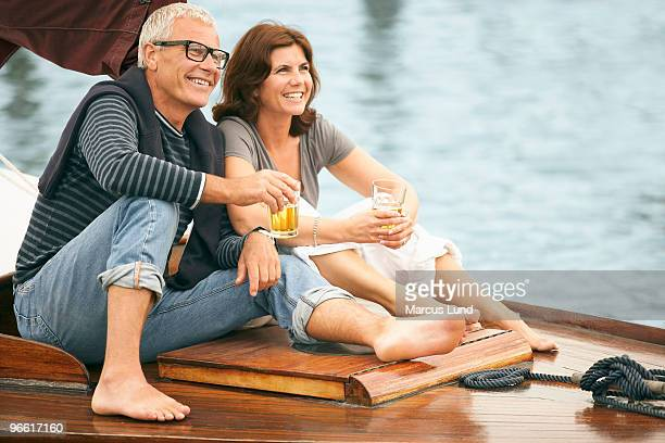 Middle aged couple drinking on boat