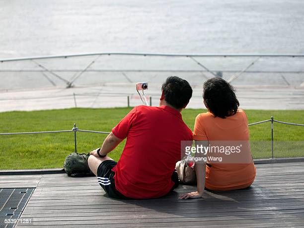 Middle aged couple from China take photo using a selfie stick at Osanbashi Pier