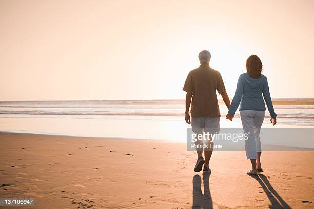 Middle aged couple on beach at sunset