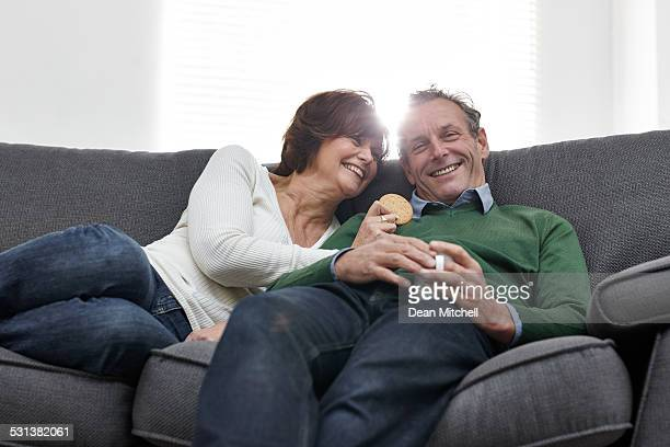 Middle aged couple relaxing together on couch smiling