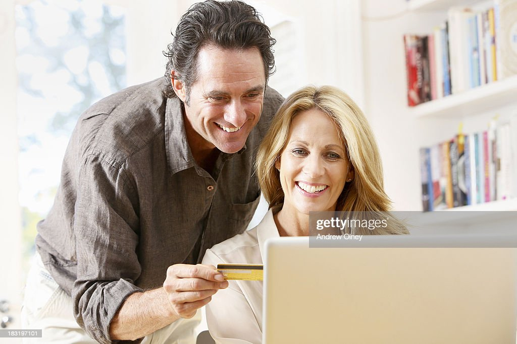 Middle aged couple shopping online : Stock Photo