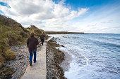 A middle aged couple walking along a rugged coastline in Balbriggan, Dublin, Ireland