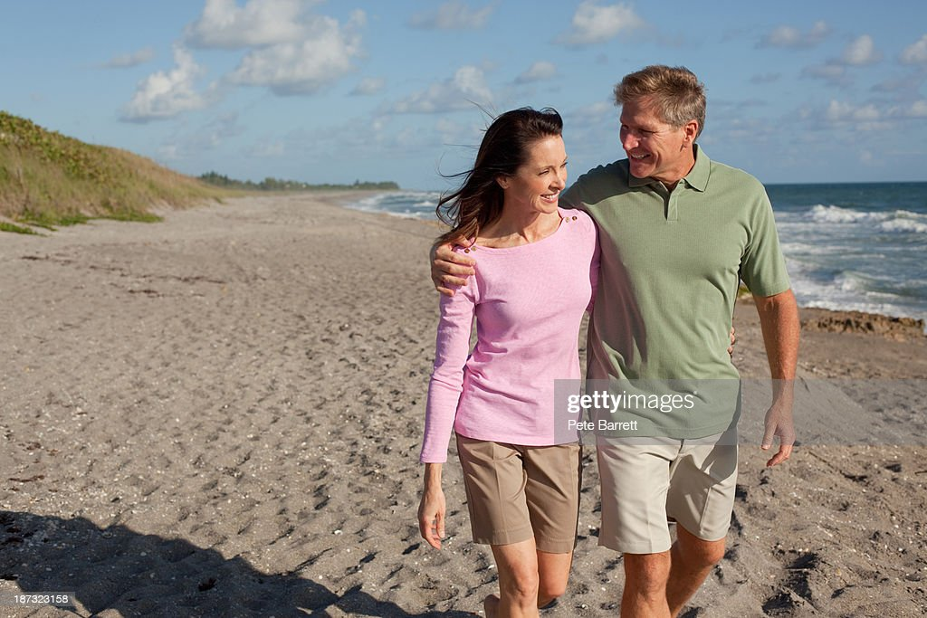 middle aged couple walking on beach : Stock Photo