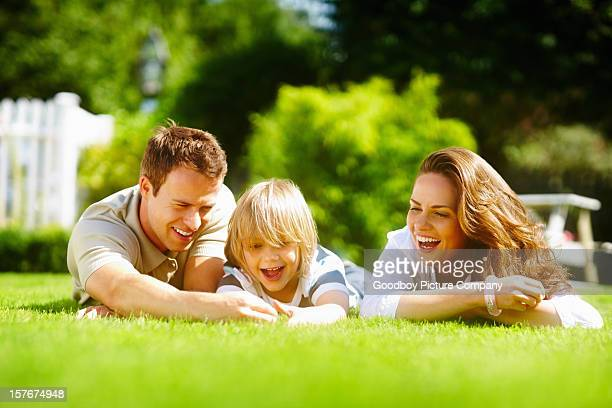 Middle aged couple with son lying on grass in park