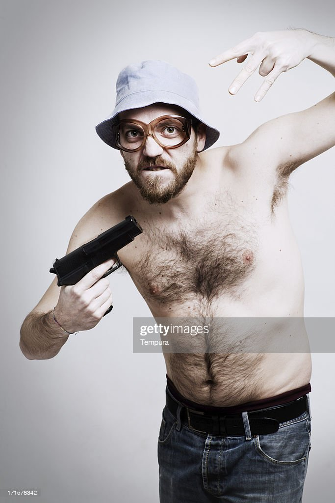 Middle aged extravagant man  gesturing holding a gun.