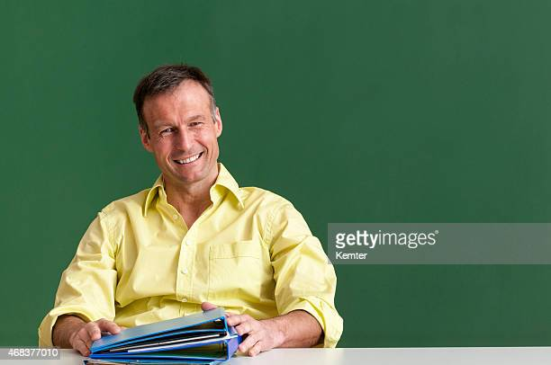 Middle aged male teacher smiling in front of blackboard.