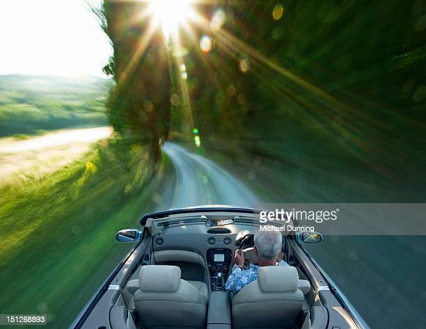 Middle aged man driving fast sports car in Tuscany
