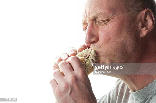 Middle aged man eating sandwich