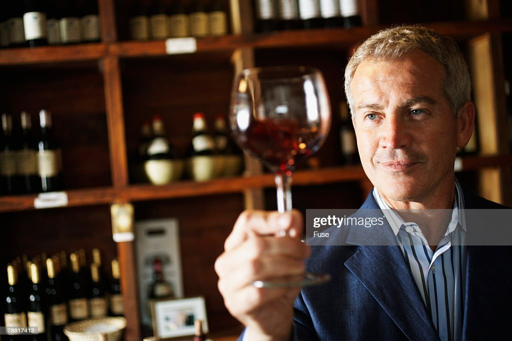 Middle Aged Man Examining Wine