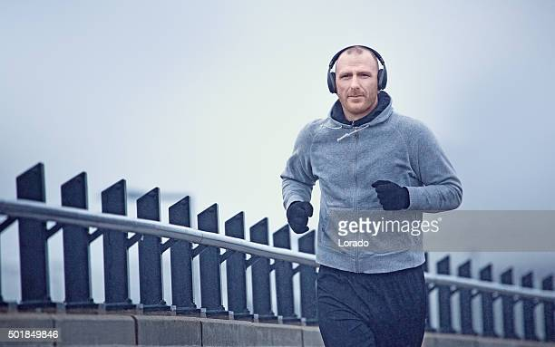 Middle aged man jogging in the city in winter
