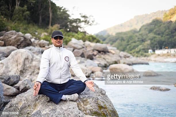Middle Aged Man Practising Meditation And Yoga at Riverside of Ganga, Rishikesh