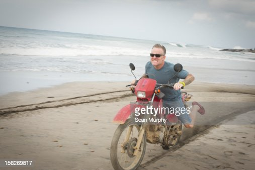 Middle Aged Man Ridding A Motorcycle on a Beach : Stock Photo