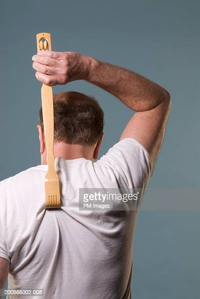 Middle aged man scratching back with back scratchier, rear view, upper half