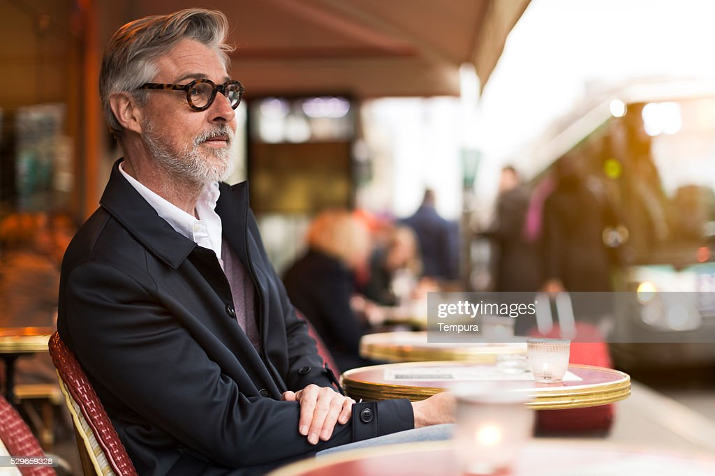 Middle aged man sitting in a french terrace. : Stockfoto