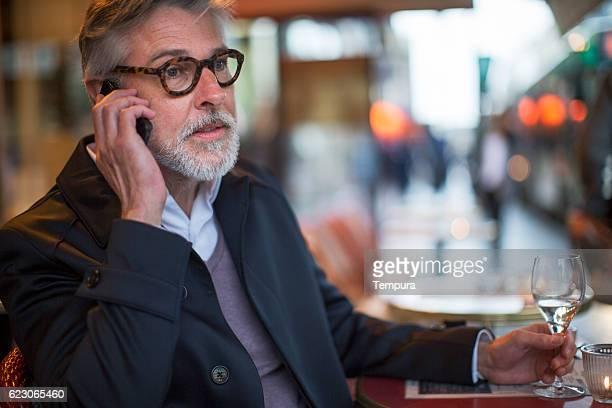 Medio invecchiato uomo seduto in una terrazza francese.