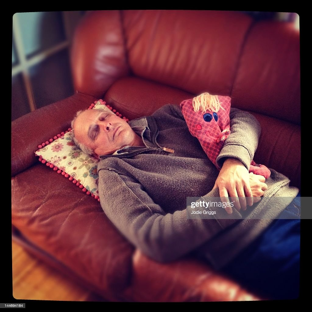 Middle aged man sleeping on chair with soft toy : Stock Photo