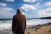 A middle aged man standing on a beach in Balbriggan, Dublin, Ireland