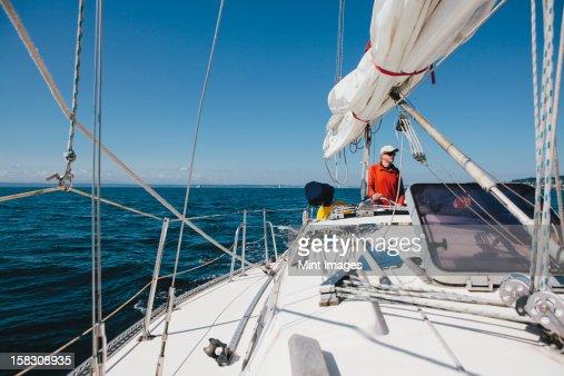 Middle aged man steering sailboat on Puget Sound, Washington, USA : Stock Photo