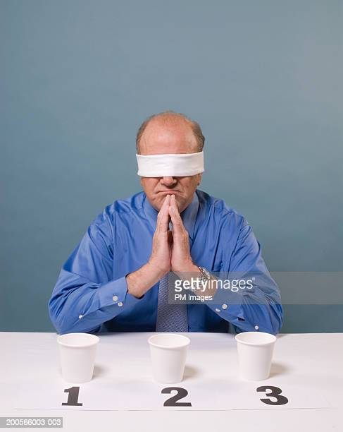 Middle aged man taking taste test, blind folded, sitting with hands clasped