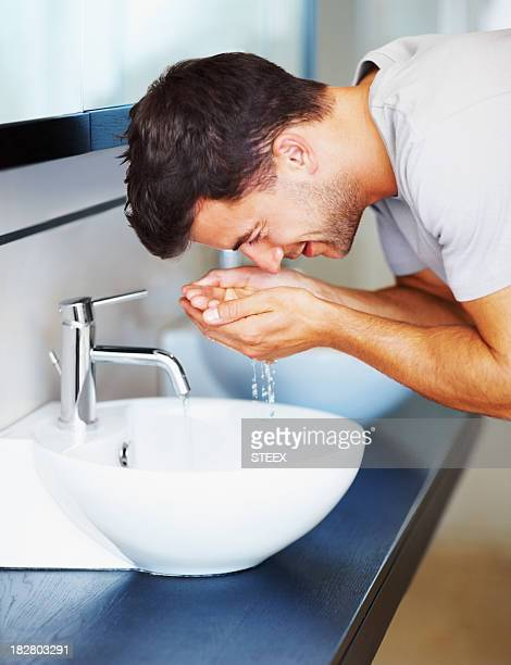 Middle aged man washes his face in bathroom