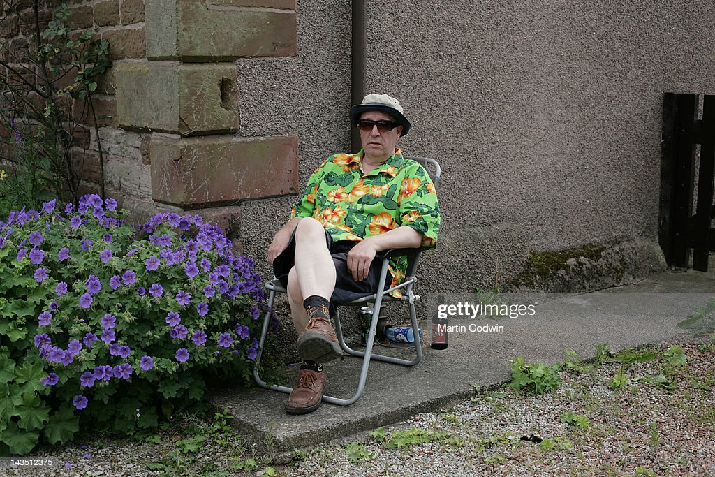 Middle aged man with dour expression, sitting in garden chair wearing loud green shirt with orange flowers and provocative nude women, and hat, with bottle of beer, next to purple geraniums, 9th June 2007