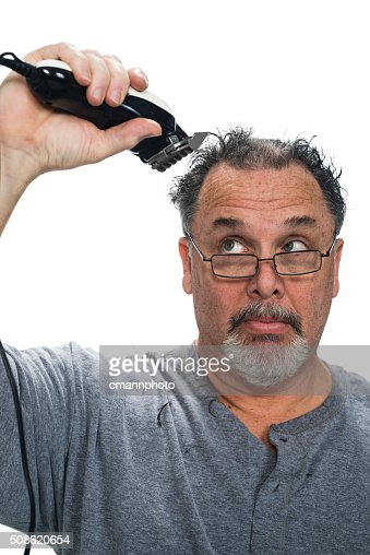 Middle aged white male giving himself a hair cut : Stock Photo
