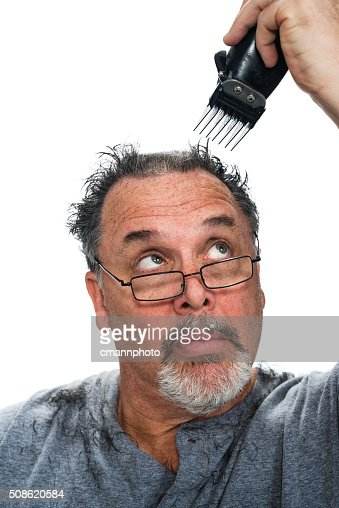 Middle aged white man giving himself a hair cut : Stock Photo