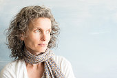 Middle aged woman with wavy grey hair and scarf looking to the side against blue background (selective focus)