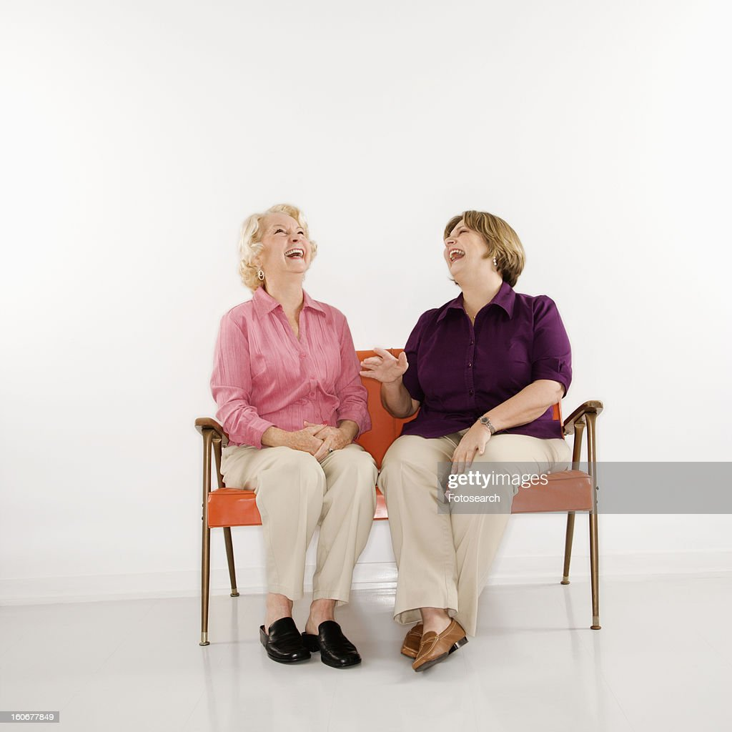 Middle aged woman and senior woman sitting and laughing