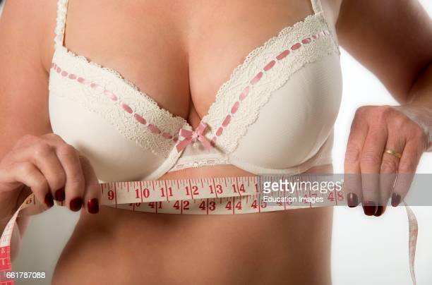 Middle aged woman checking under bra measurement using a tape measure