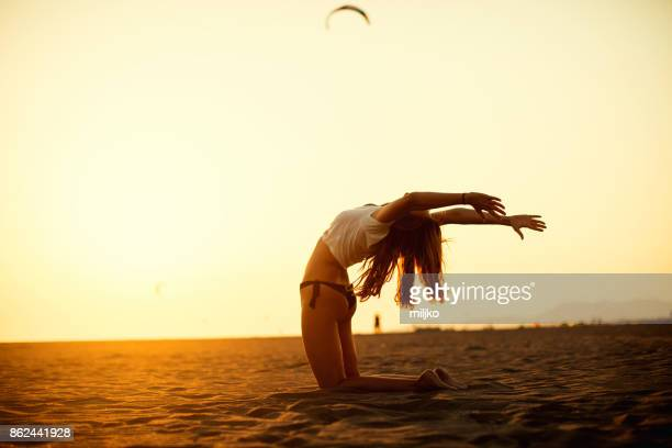 Middle aged woman doing yoga at the beach