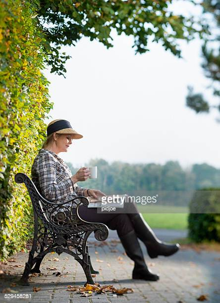 middle aged woman enjoying the autumn sun with straw hat