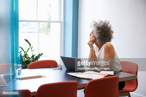 Middle aged woman looking out of the window in the boardroom : Stock Photo