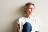Middle aged woman in cream top and jeans sitting on floor looking pensive against neutral background (cropped and selective focus)