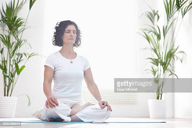 Middle aged woman meditating at home