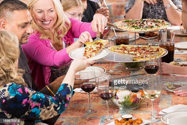 Middle aged woman passing pizza to her friends at restaurant