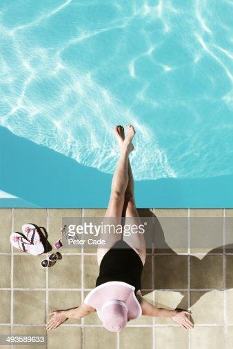 Middle aged woman relaxing at edge of pool