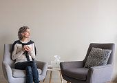 Middle aged woman seated looking pensive in living room with second empty armchair (selective focus)