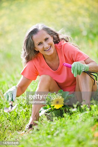 Middle Aged Woman Sitting In Flowers : Stock Photo