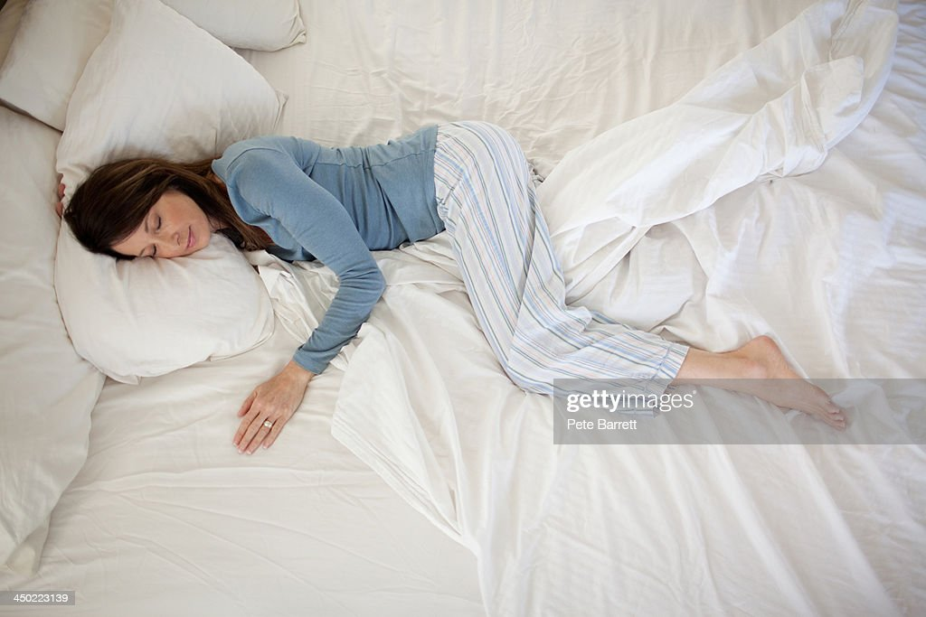 middle aged woman sleeping in bed