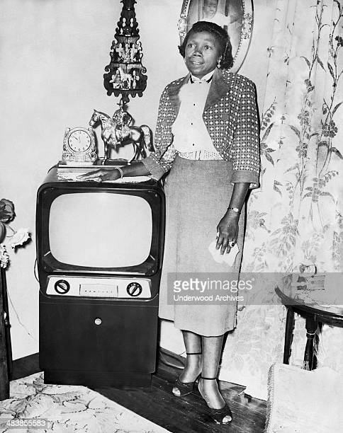 A middle aged woman stands proudly by her Admiral television set in her living room San Francisco California early to mid 1950s