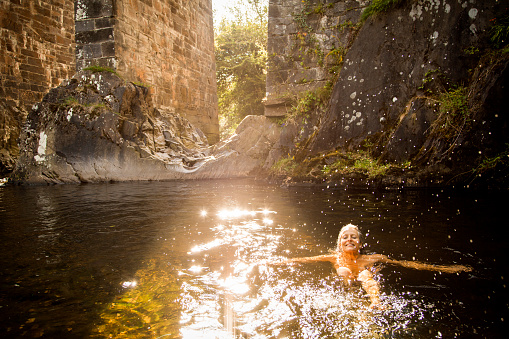 Middle aged woman swimming in the river
