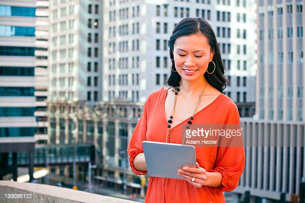 A middle aged women holding a tablet device.