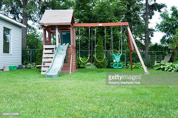 Middle class house backyard with a little playground for children and a nice lawn