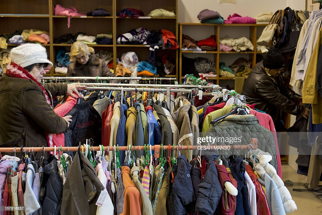 GROULT 'Middle class to underclass in impoverished Spain' Low-income people buy clothes for one euro piece at the Caritas charity shelter in Burgos, northern Spain, on November 28, 2012. As the first snow of winter falls, a crowd squeezes through the door of the charity shelter. Women, immigrants, the homeless and jobless -- the swelling ranks of Spain's economic casualties.