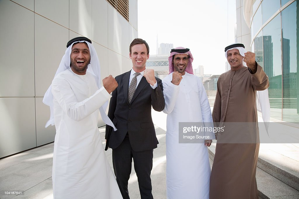 Middle eastern and western businessmen cheering
