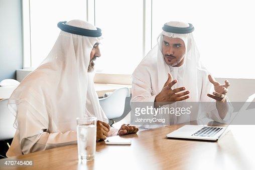 Medio Oriente en ropa tradicional árabe empresarios hablando en la oficina